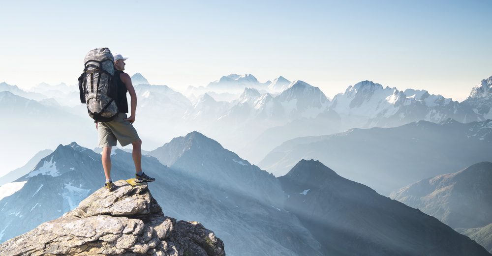 человек на краю скалы, горы, рюкзак, via shutterstock