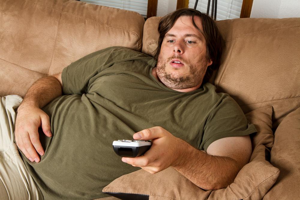 мужчина с лишним весом на диване, via shutterstock