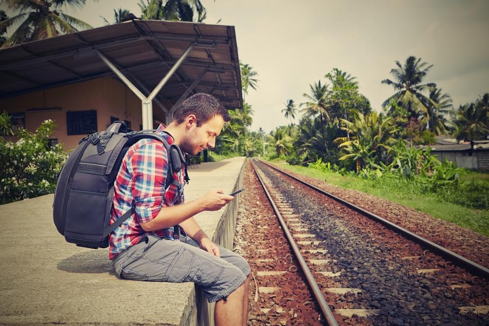 молодой мужчина на остановке, via shutterstock.