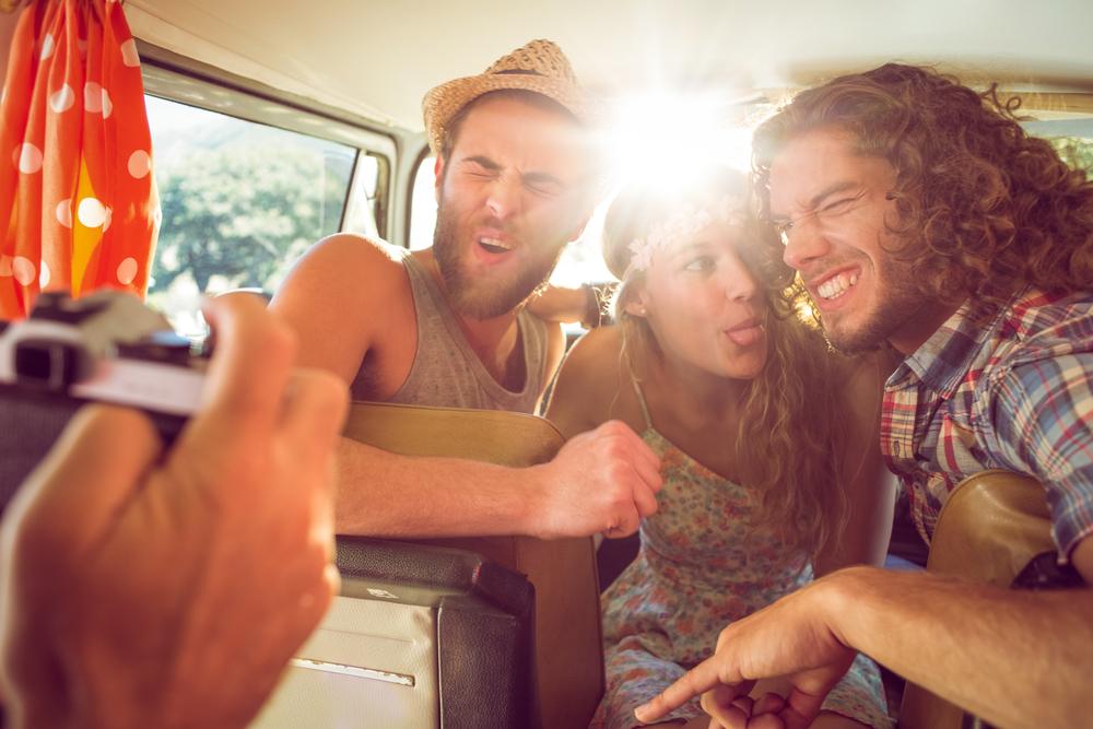 друзья в машине фотографируются, via shutterstock