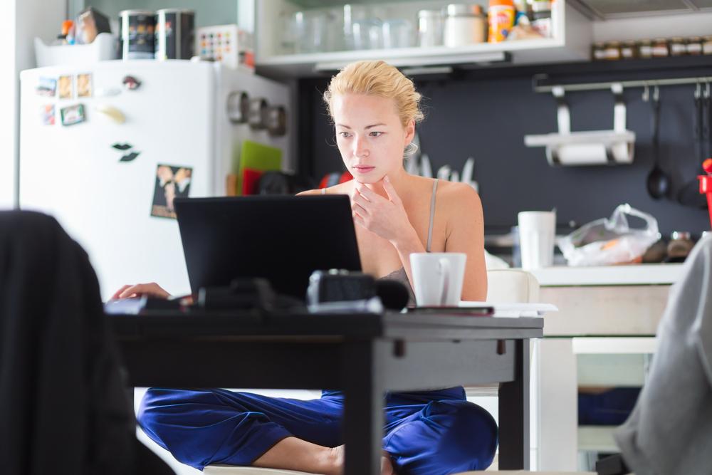 молодая девушка сидит за ноутбуком, via shutterstock