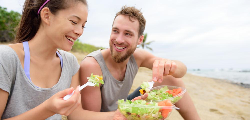молодая пара ест на берегу, via shutterstock.
