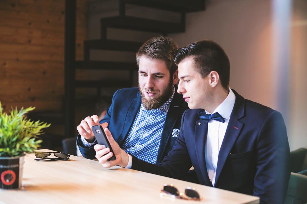 молодые парни смотрят на смартфон, via shutterstock