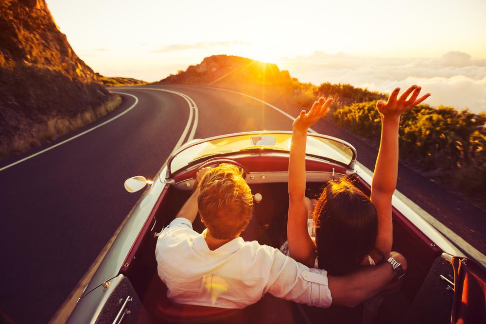 молодая пара едет на автомобиле, via shutterstock.
