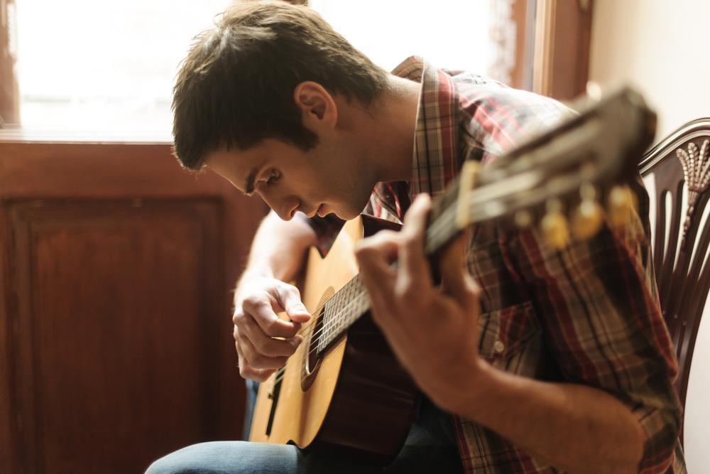 молодой парень играет на гитаре, via shutterstock