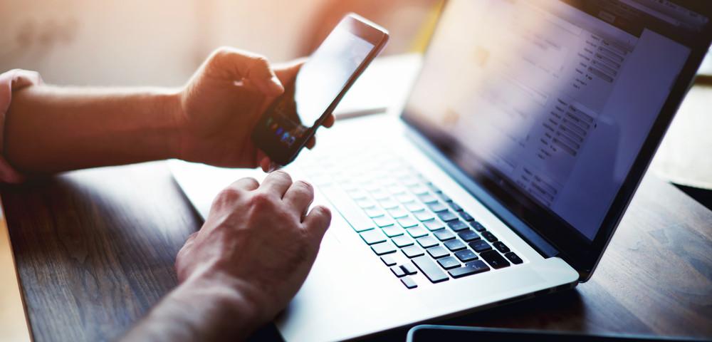 мужчина держит в руках телефон перед компьютером, via shutterstock