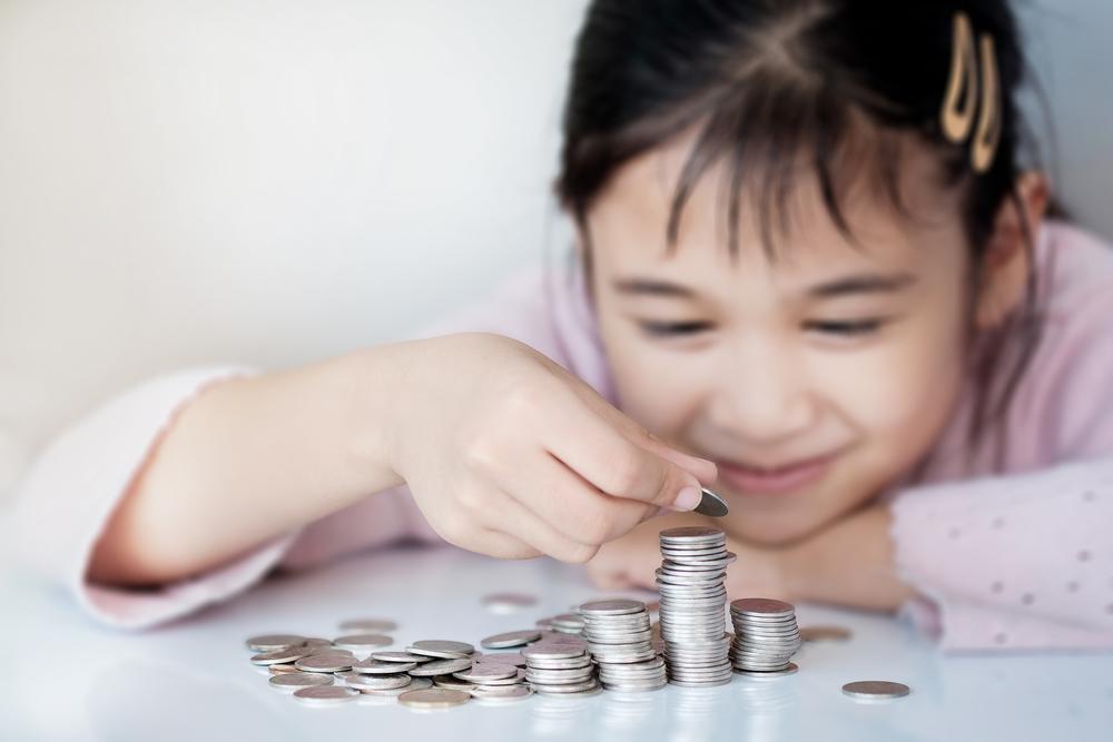 девочка складывает монеты, via shutterstock