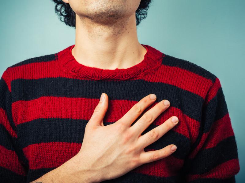 мужчина держит руку на груди, via shutterstock