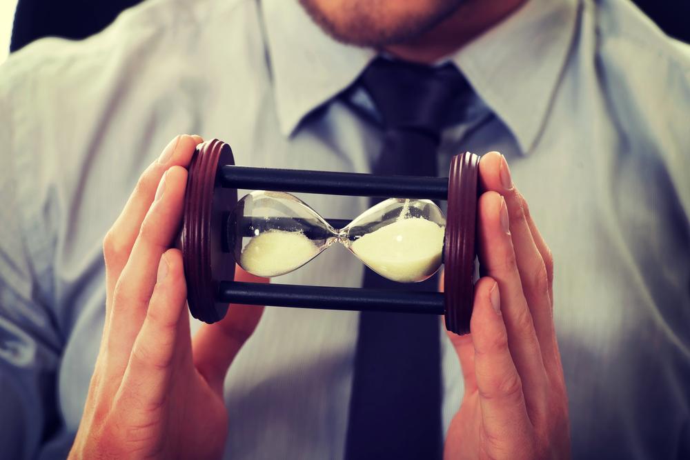 мужчина держит в руках песочные часы, via shutterstock