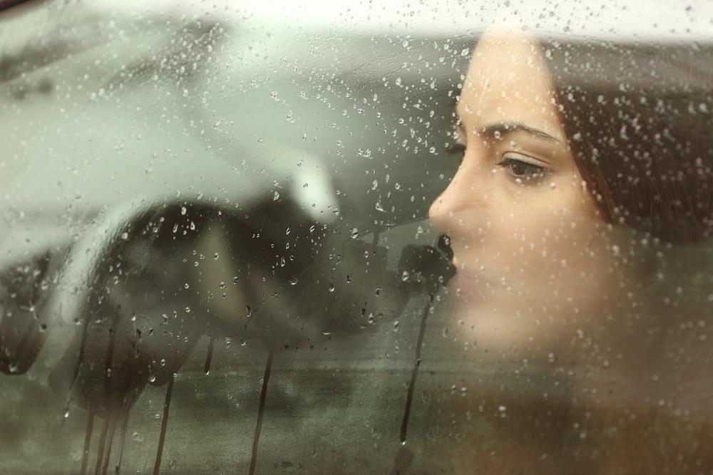 девушка смотрит в окно, via shutterstock