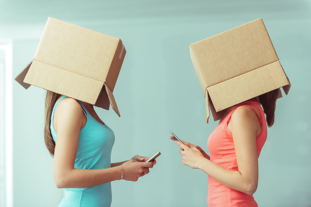 девушки с телефонами в руках, via shutterstock.