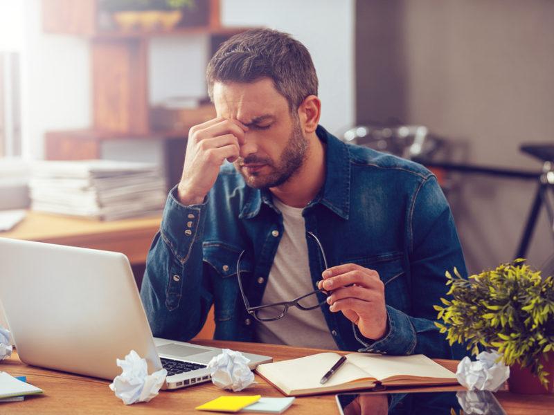 мужчина за столом усталость, via shutterstock