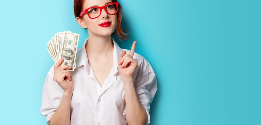 девушка с деньгами в руках, via shutterstock