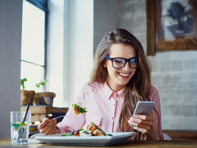 девушка держит в руке телефон, via shutterstock