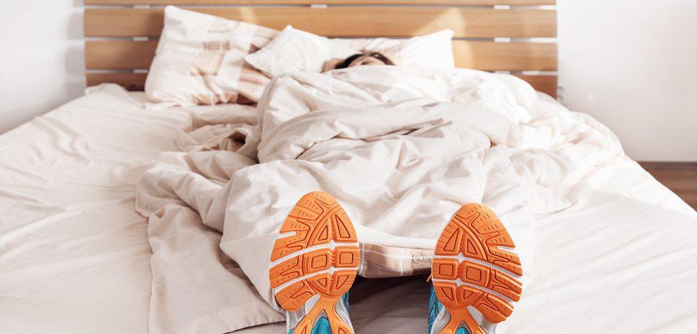 в кроссовках на кровати, via shutterstock