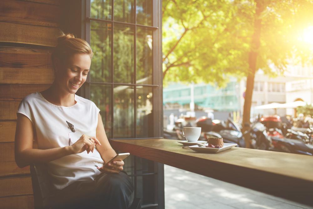 девушка в кафе с телефоном, via shutterstock