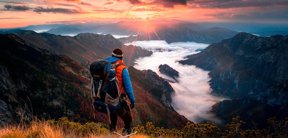 Мужчина в горах смотрит на закат