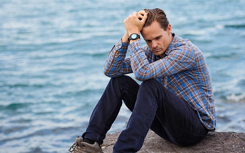 Мужчина задумался возле океана